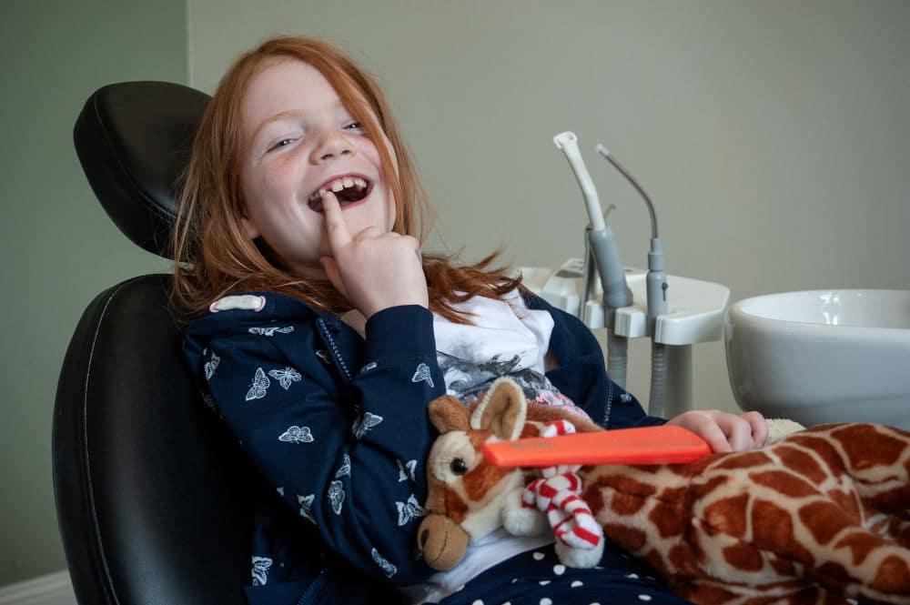 Kind im Behandlungsstuhl zeigt auf Zahnlücke